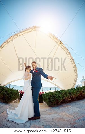 Young wedding couple enjoying romantic moments dansing and have fun outside against modern buildings. Fisheye lens