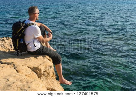 Hiker with bare feet sits on a rocky sea shore resting after a walk and looks into the distance. Clear emerald sea