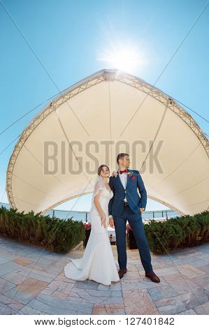 Young wedding couple enjoying romantic moments outside against modern buildings. Fisheye lens