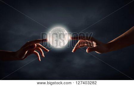 Finger reaching moon planet