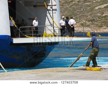 ISLAND OF SIFNOS, GREECE - AUGUST 24, 2007: Dock worker is pulling a rope while ship crew is standing on a docking platform of approaching ferry Agios Georgios, Ventouris Sea Lines.