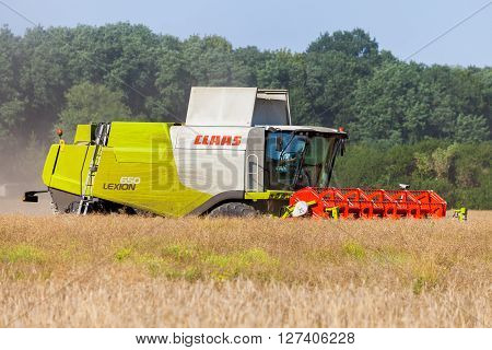 BURG / SAXONY-ANHALT / GERMANY - JULY 2015: german Claas Lexion 650, combine harvester works on a field in Burg / Germany at July 2015.
