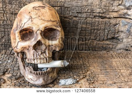 Human skull smoking cigarette with smoke on wooden background; smoking addiction concept