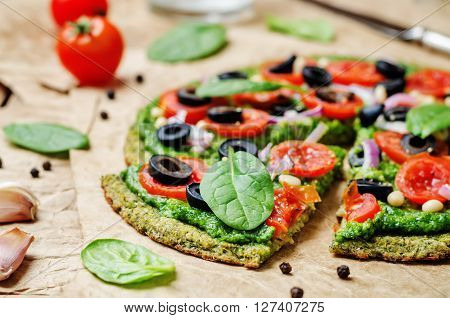 vegan broccoli zucchini pizza crust with spinach pesto tomatoes onion and olives