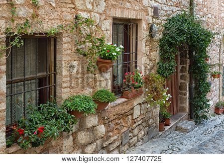 Plants in pots on narrow streets of the ancient city of Spello Umbria Italy