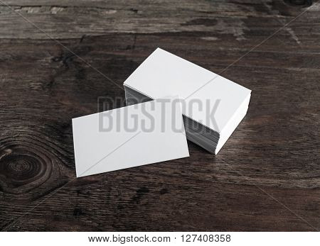 Blank white business cards on dark wooden background. Mock-up for branding identity. Blank template for design presentations and portfolios.