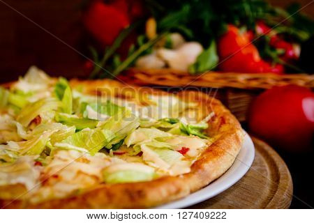 Vegetarian pizza and fresh vegetables in caffe
