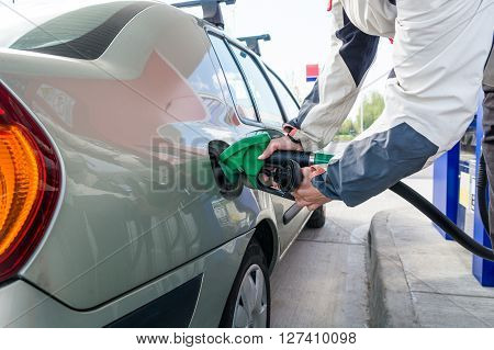 Pumping gas at gas station. Hand holding fuel nozzle. Gasoline economy concept.