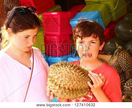 pre teen boy smell durian - tropical fruit with good taste but bad smell