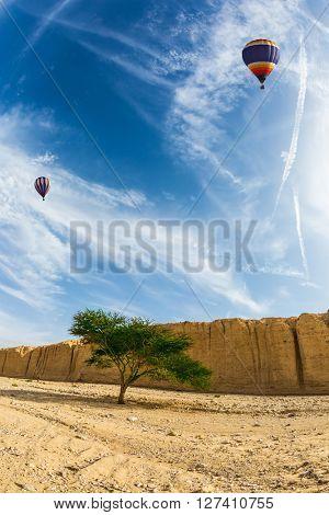 Huge two multi-colored balloons over the hot desert. Stone desert near the seaside resort of Eilat