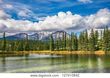 The lake is surrounded with evergreen fir-trees. The small lake in the Rocky Mountains of Canada