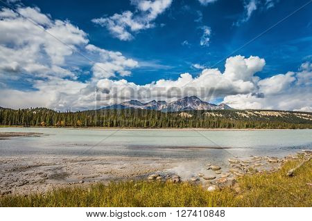 Beneaped Medicine Lake in the fall. Evergreen forests and snow-capped Rocky Mountains of Canada