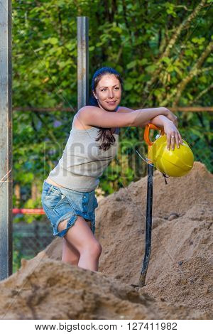 Pretty young woman builder digging with shovel industrial temwork