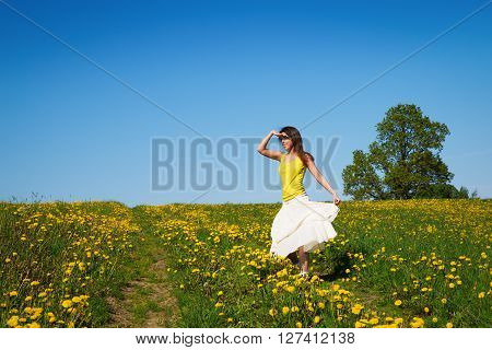 Young Woman On A Meadow Of Dandelion In Spring Time
