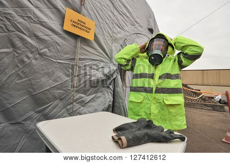 Saint-Petersburg Russia April 6 2016: During the exercise to eliminate radiation contamination man tries on a gas mask and protective suit in the item sanitization