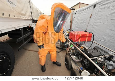 Saint-Petersburg Russia - April 6 2016: A man in an orange protective kit next to the installation of a mobile station for elimination of radiation and chemical accidents at industrial facilities.