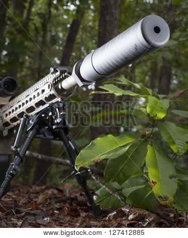 Silencer on the end of a modern sportiong rifle in the forest