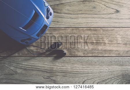 CD player and earphones on wooden plank under warm light
