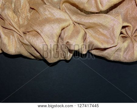 the Golden cloth is laid in the crease, on a black background