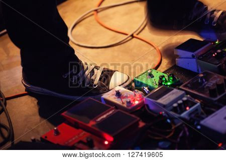 Feet Of Guitar Player With Set Of Effect Pedals