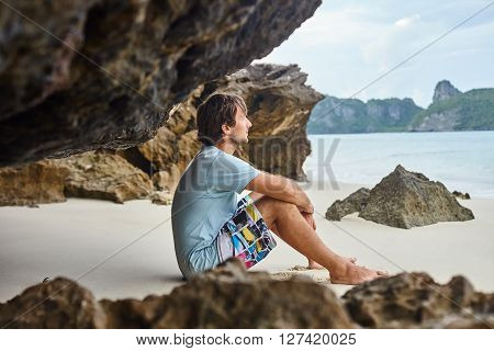 Handsome man sitting on the beach in cave. Relax concept
