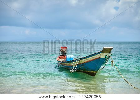 Boat tethered near the shore of tropical beach, Thailand