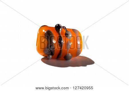 Hand made orange and brown glass bead on white background