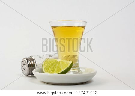 Two gold tequila shots with lime and salt on the white background. Tequila. Gold Mexican tequila. Tequila shot