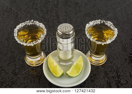 Two gold tequila shots. Tequila shot. Gold Mexican tequila. Tequila