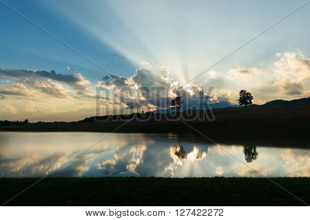 Light beam over mountain silhouette landscape refection