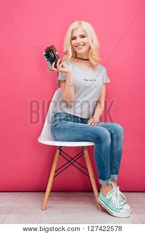 Happy young woman sitting on the chair and holding photo camera over pink background