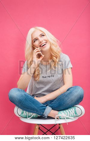 Smiling blonde woman talking on the phone over pink background