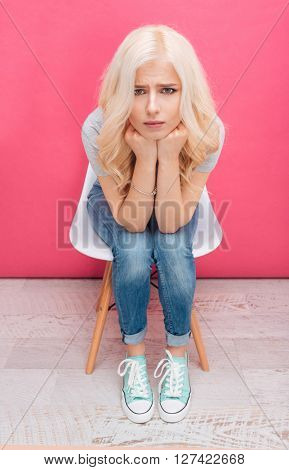Unhappy blonde woman sitting on the chair and looking at camera over pink background