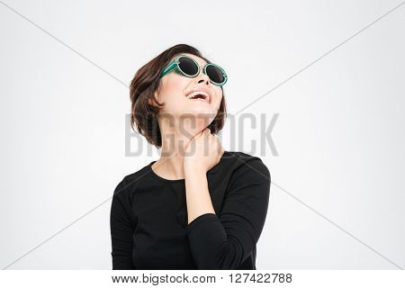 Happy woman in sunglasses posing isolated on a white background