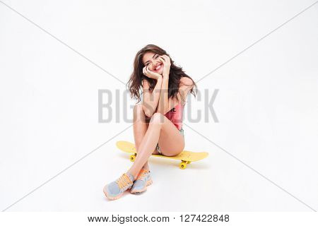 Smiling pretty woman sitting on the skateboard isolated on a white background