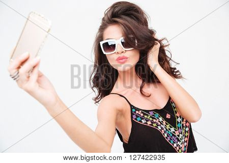 Charming stylish woman making selfie photo on smartphone isolated on a white background