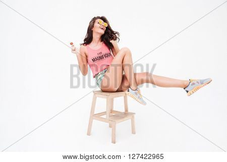 Stylish woman in sunglasses and candy posing on the chair isolated on a white background
