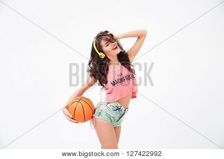 Cheerful attractive woman holding basketball ball and listening music in headphones isolated on a white background
