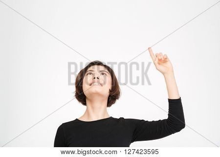 Smiling young woman pointing finger up isolated on a white background