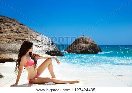 Bikini Model Resting On Tropical Beach. Outdoor Portrait Of Beautiful Brunette Woman Lying On White