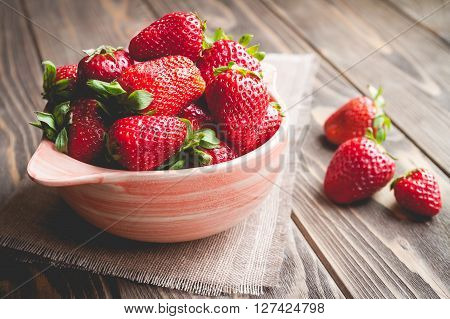 fruit. Fresh red strawberries in a pink bowl on old wooden background