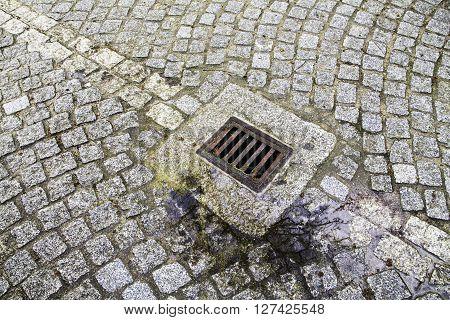 closeup drain grid on the urban road pavement