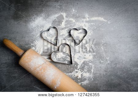 Flour, Cookie Cutters Shaped As Heart And Rolling Pin On A Stone Table
