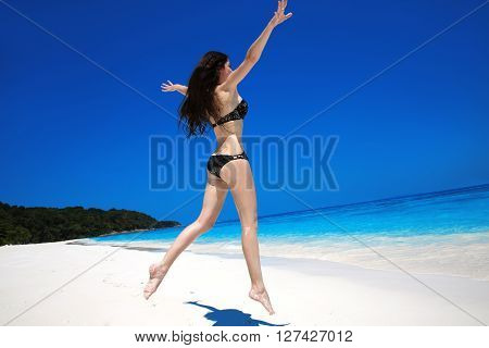Brunette Woman Jumping On Tropical Beach. Summer Vacation. Happy Girl Running On Exotic Seashore Isl