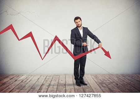 Disappointed businessman pointing to red graph arrow down.