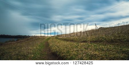 road in a field on the background of dark sky before the rain