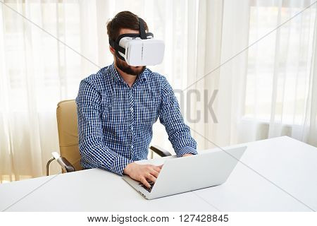 Young handsome man is watching something in virtual reality glasses while working on his laptop