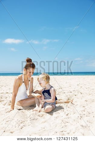 Smiling Mother And Girl In Swimsuits At Sandy Beach Playing