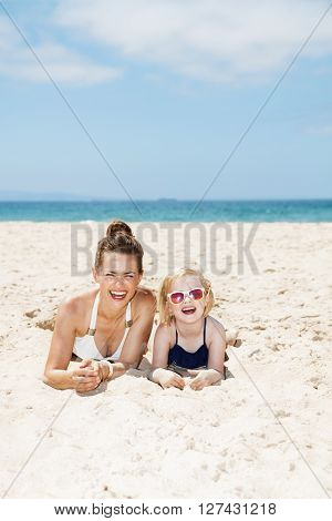 Happy Mother And Child In Swimsuits Laying On Sandy Beach