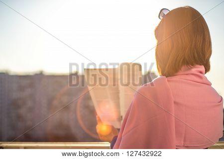 Woman reading magazine horizontal balcony, home, city